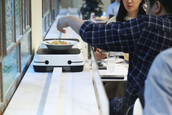 More than 500 restaurants around the world already use robots that serve three coffees in 40 seconds, make different types of noodles, an omelette or a perfect salad, especially in countries like the US, Japan, South Korea or Singapore. South Korea has been an early adopter and automation enthusiast, with the highest density of industrial robots in the world in 2017, with 710 robots per 10,000 factory workers, according to the International Robotics Federation. In the photo, Baedal Minjok, delivery company of Korea Opens New Restaurant baked by self-driving robot.